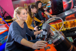 Indoor Portland Fun: Woman smiling on arcade motorcycle
