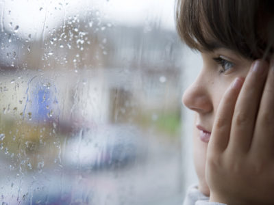 young child looking out of window on rainy day